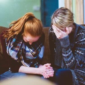 Dos mujeres rezando y llorando juntas.