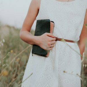 A woman in a white dress holding a Bible.