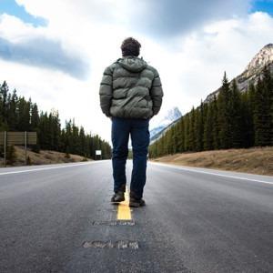 hombre de pie un camino frente a las montañas Crédito de la foto Anna Claire Schellenberg en unsplash.com