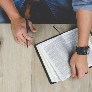 persona que sostiene la biblia con la pluma. Crédito de la foto de Ben White en unsplash.com