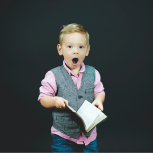 An image of a little boy with a surprised face and holding a Bible.