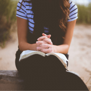 A woman sitting outside with folded hands on an open Bible.