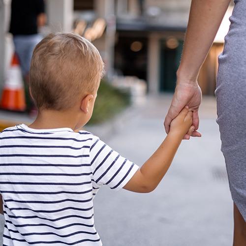 Imagen de la madre sosteniendo la mano de un niño.