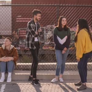 Foto de jóvenes parados junto a una valla hablando entre ellos por Eliott Reyna en Unsplash