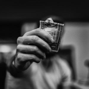 Foto de un hombre con dinero delante de él por Lucas Favre en Unsplash