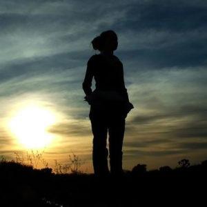 Siluetas de una mujer de pie frente a la puesta de sol