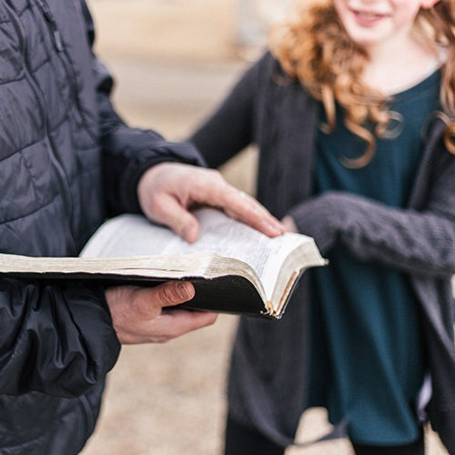 padre enseñando a su hija sobre la Biblia
