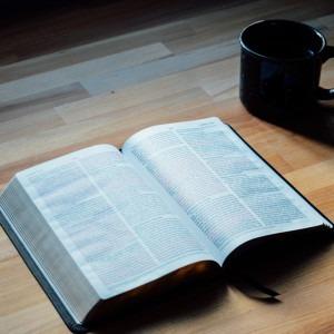 Foto de una Biblia junto a una taza de café por Ryan Riggins en Unsplash