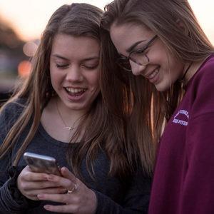dos chicas jóvenes en smartphone