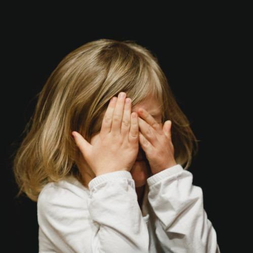 Foto de una niña cubriéndose la cara con las manos por Caleb Woods en Unsplash