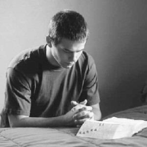 Joven rezando cerca de una Biblia.