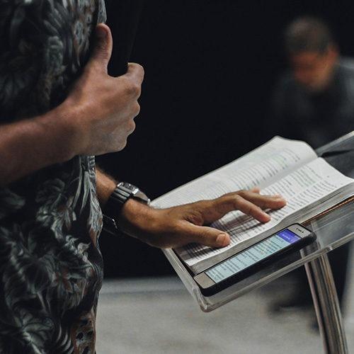 Persona de pie mientras abre la Biblia en el escenario.