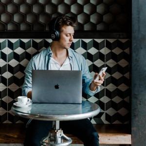 Foto de un chico en una cafetería con auriculares trabajando en la computadora mirando el teléfono celular por Austin Distel en Unsplash