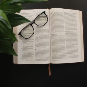 An open Bible with glasses on top sitting next to a green plant.