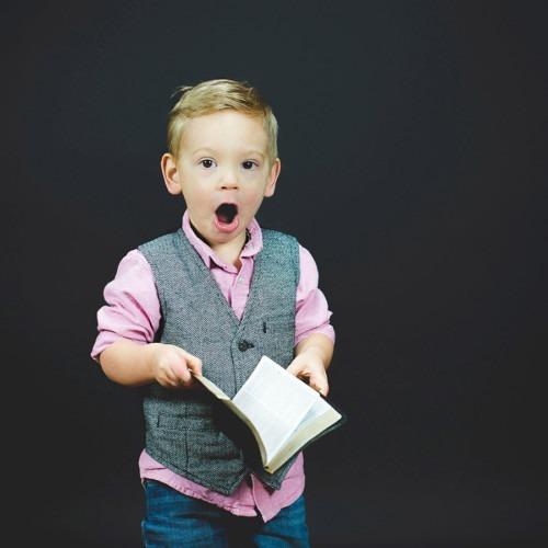 Foto niño emocionado sosteniendo un libro abierto por Ben White en Unsplash