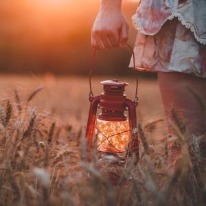Foto de una mujer sosteniendo una linterna en un campo de trigo por Guilherme Stecanella en Unsplash