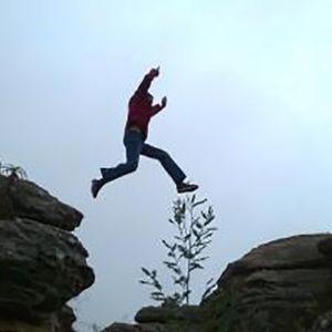 Foto de un hombre saltando rocas.