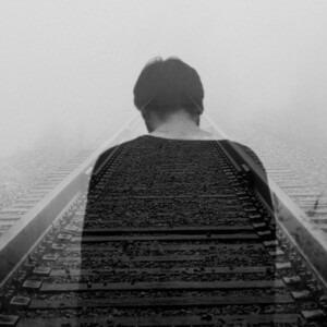 Una persona triste mirando las vías del tren.