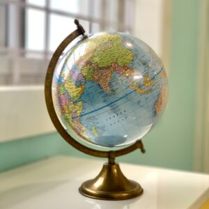 An image of a globe on a desk in front of a window.