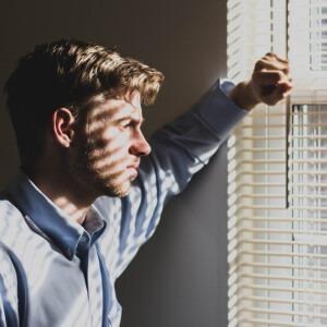 Hombre preocupado mirando por una ventana.