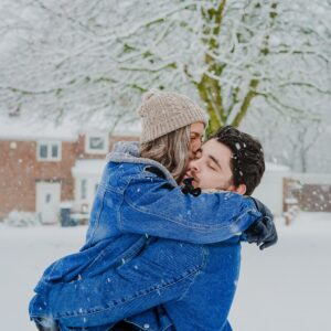 A man holding a woman while she kisses his cheek in the snow.