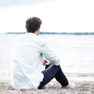 Foto de un hombre sentado en el suelo junto al agua por Stefan Spassov en Unsplash