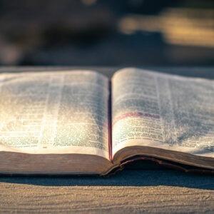Biblia abierta sobre mesa de madera.