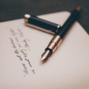 Pluma fuente sobre una carta con escritura caligráfica.