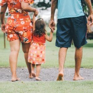 Familia caminando sosteniendo de la mano a una pequeña niña.