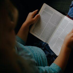 A little girl holding an open Bible.