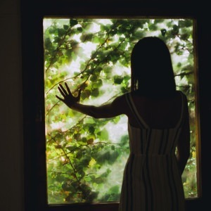 Photo of woman facing a window by Maria Teneva on Unsplash