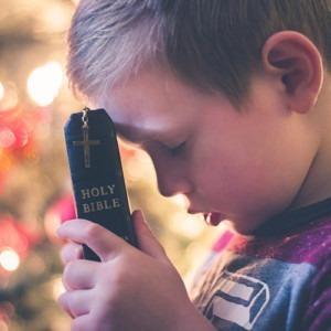 Niño orando mientras sostiene la Biblia en la frente. Crédito de la foto Anna David Beale en unsplash.com