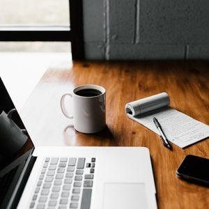 Computadora, taza de cerámica blanca y teléfono inteligente negro sobre mesa.