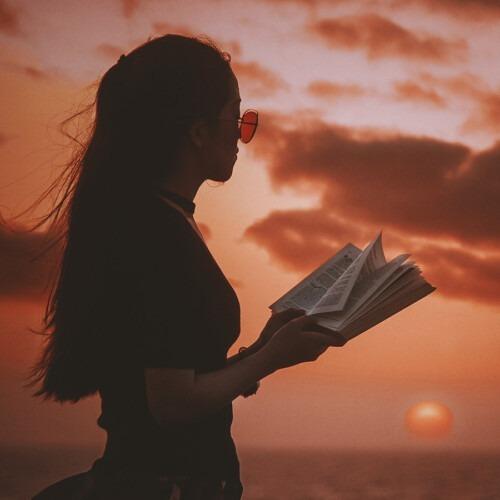 Una mujer sosteniendo la Biblia y mirando la puesta de sol.