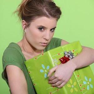 Chica sosteniendo un regalo firmemente