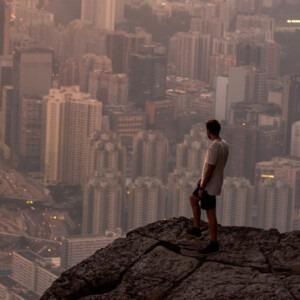 Hombre de pie sobre una cornisa de montaña con vistas a la ciudad.