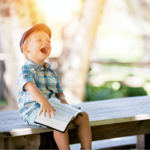 A little boy sitting on a picnic table with an open Bible and laughing.