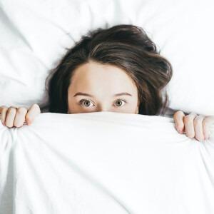 Mujer temerosa que mira a escondidas debajo de una sábana.