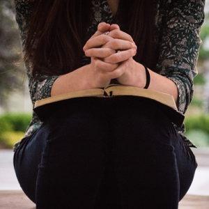 Manos de mujer dobladas en oración sobre una Biblia.