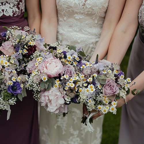 Imagen de damas de honor con ramos de flores.