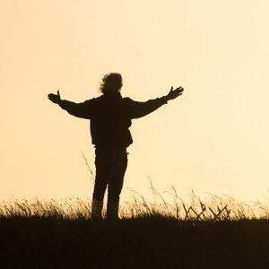 La silueta de un hombre que se coloca en un campo con los brazos se abre de par en par.