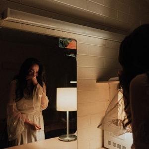Imagen de una mujer llorando mirando en un espejo