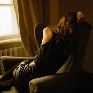 Viuda sentada de lado en una silla llorando.