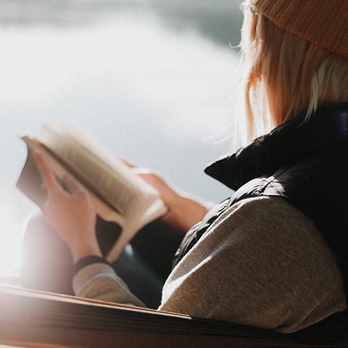 Imagen de la espalda de una persona que lee la Biblia.