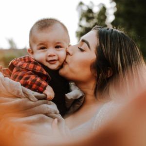 Foto de una madre besando a su bebé por Omar López en Unsplash