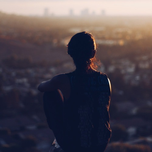 Foto de mujer pacífica con vistas a la ciudad por Christopher Sardegna en Unsplash