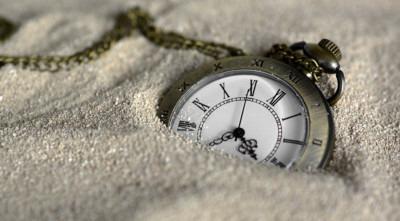 Imagen de un reloj de bolsillo en la arena de annca de Pixabay