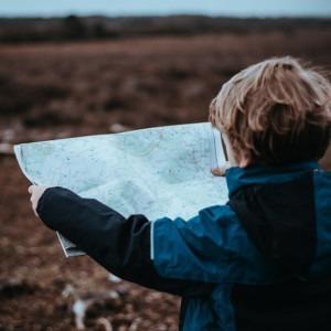 Foto de un niño sosteniendo un mapa por Annie Spratt en Unsplash
