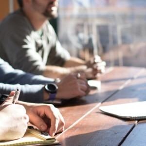 Foto de hombres sentados en una mesa discutiendo el discipulado por Dylan Gillis en Unsplash