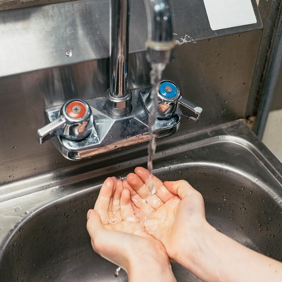 Foto persona lavándose las manos por Allie Smith en Unsplash